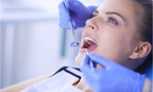 The dentist cleans the patient's mouth and teeth.